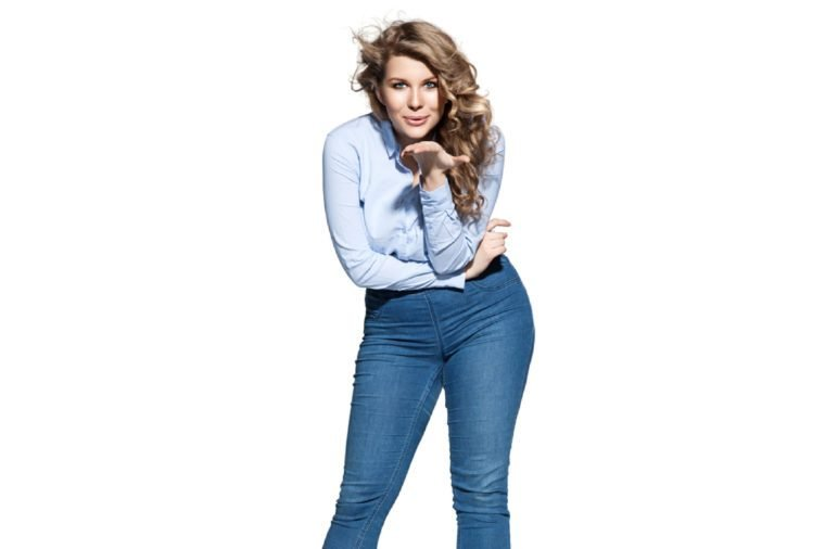 Beautiful plump woman in jeans and a denim shirt sends air kiss