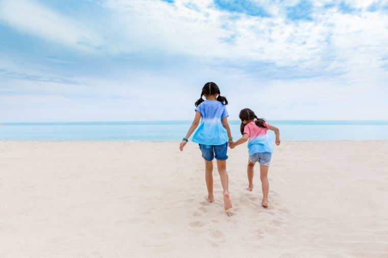 Two Asian sister enjoy playing on beach, Two little asian girls enjoy playing and walk on beach in day time,Two asian little girls enjoy playing on nice beach