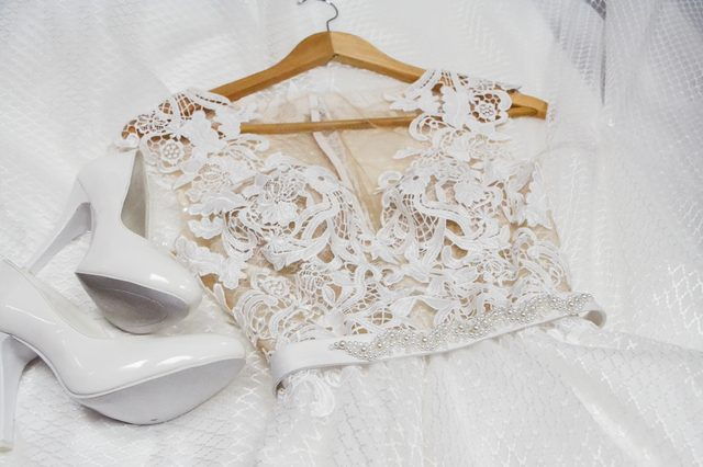 Fashion wedding dress is on a hanger and white bridal shoes. View from above. Clothes for bride. Fashion look.