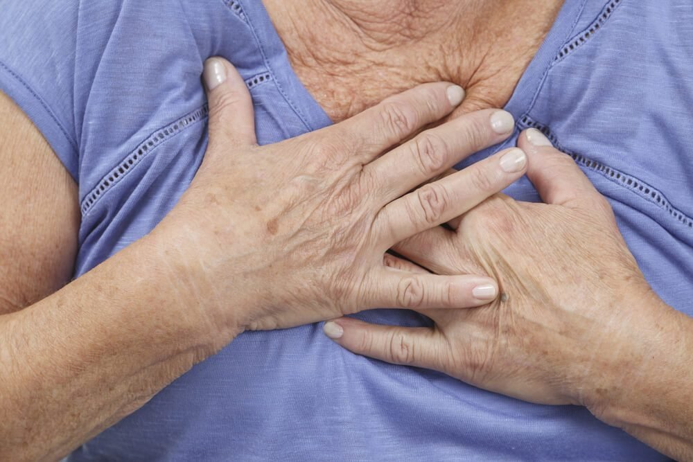 Old woman experiencing chest pains, having a heart attack or stomach acid
