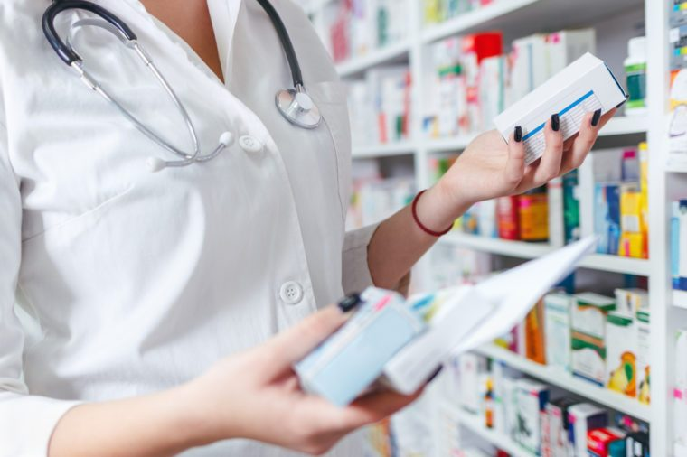 Closeup hand of woman pharmacist with prescription and medicine at drugstore