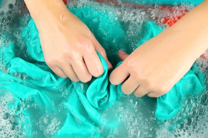 Female hands washing color clothes in basin