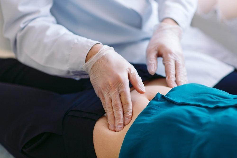 doctor pressing on patient's abdomen