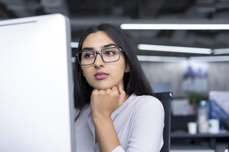 Serious young businesswoman working at computer