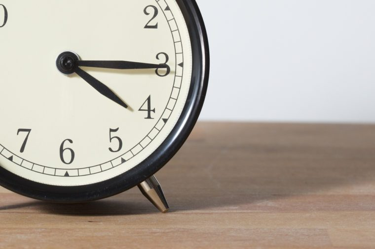 It is 4:15 o'clock am or pm. The time is quarter past four. Get off work. A retro clock isolated on a wooden table and a white background. Image taken in a small angle to create perspective