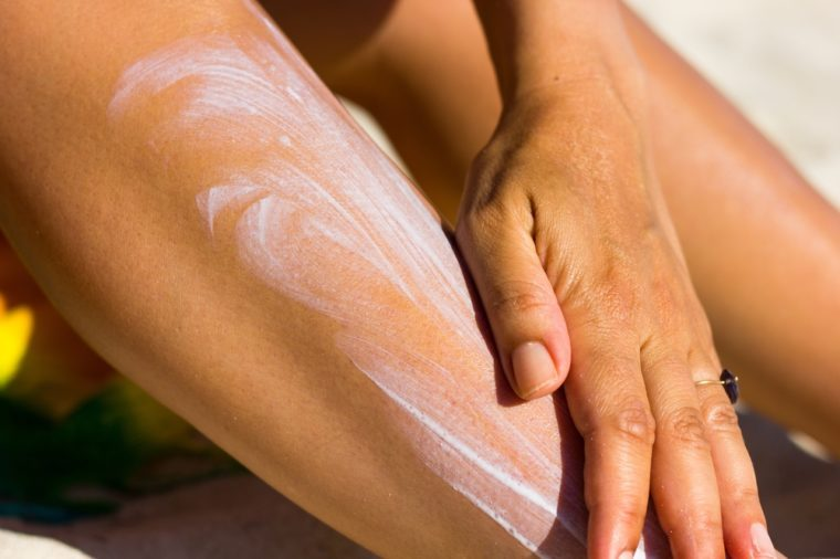 Close up on woman's hand spreading sun cream on her leg at the beach on a warm, sunny day. Sunblock, skin care protection concept