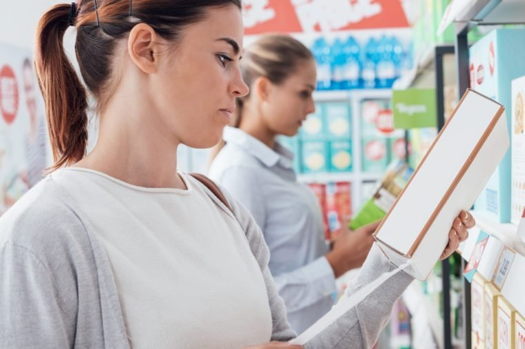 Woman shopping at the supermarket and reading nutrition facts and ingredients on a box