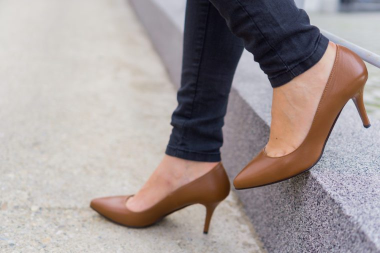 Woman wearing black jeans and high heels shoes brown