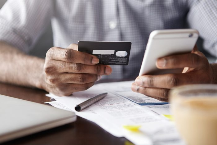 Close-up view of African man's hands holding plastic credit card and smart phone. Dark-skinned businessman using mobile banking application on his gadget while paying bills at cafe online via internet