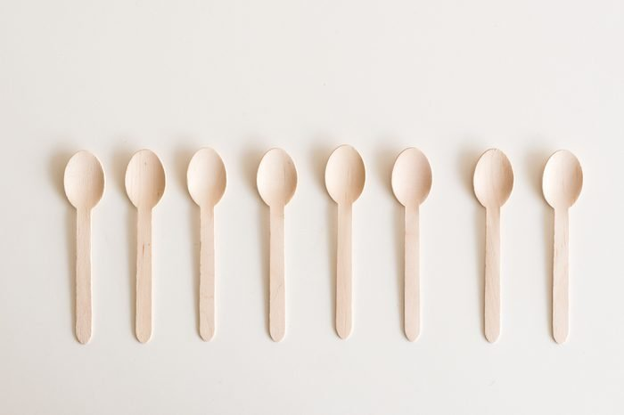 High angle view of bamboo spoons arranged in a row on white table
