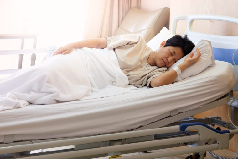 Asian woman sleeping In hospital bed, Morning sun shines into the room, AF point selection and blur.