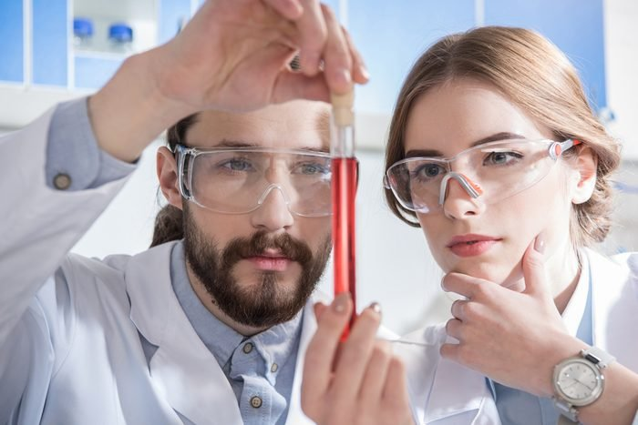 Two young scientists holding chemical sample in test tube