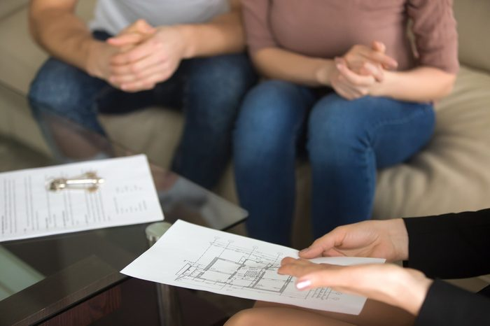 Close up view of female realtor showing to young couple of buyers flat plan on the sheet of paper sitting on sofa indoors, discussing buying apartment, considering flat purchase, interior layout