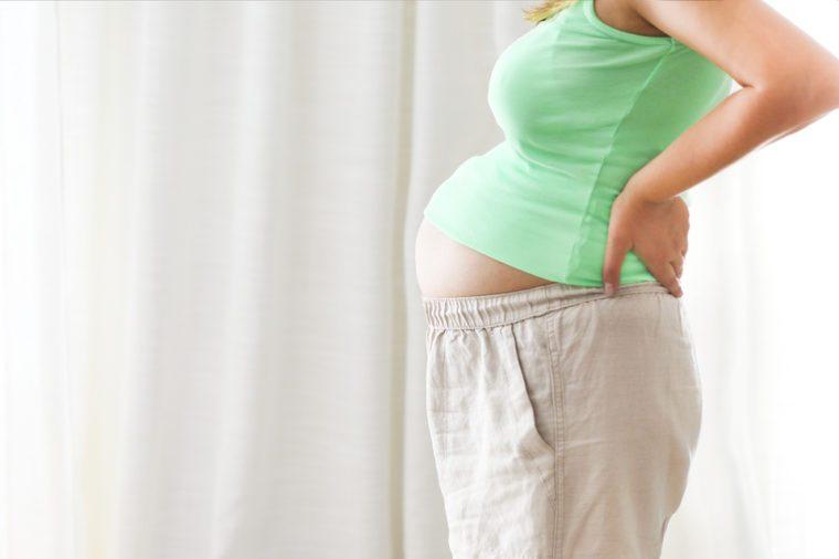 Pregnancy, motherhood- close up of happy pregnant woman indoors