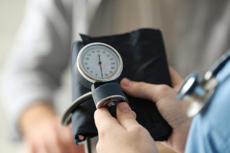 Medical assistant preparing to measure patient's blood pressure, closeup