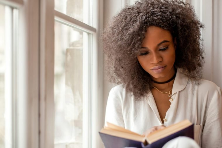 Beautiful african american young woman sitting by the window and reading a book.