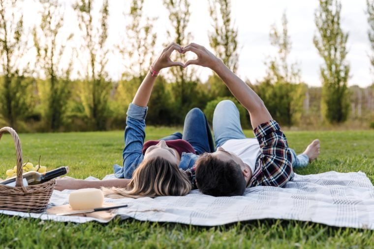 Happy couple in love, lying on the park and enjoying the day together