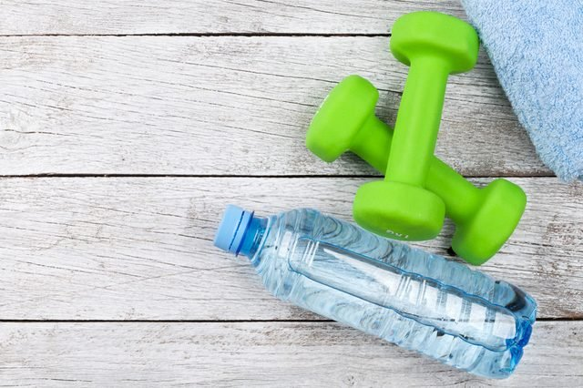 Fitness concept. Dumbbells and water bottle on wooden background. Top view with space for your text