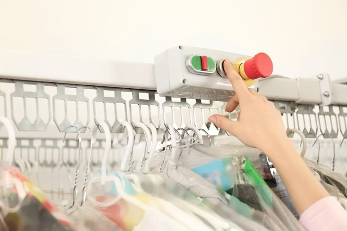 Female laundry worker pushing button on rack at dry-cleaning, closeup