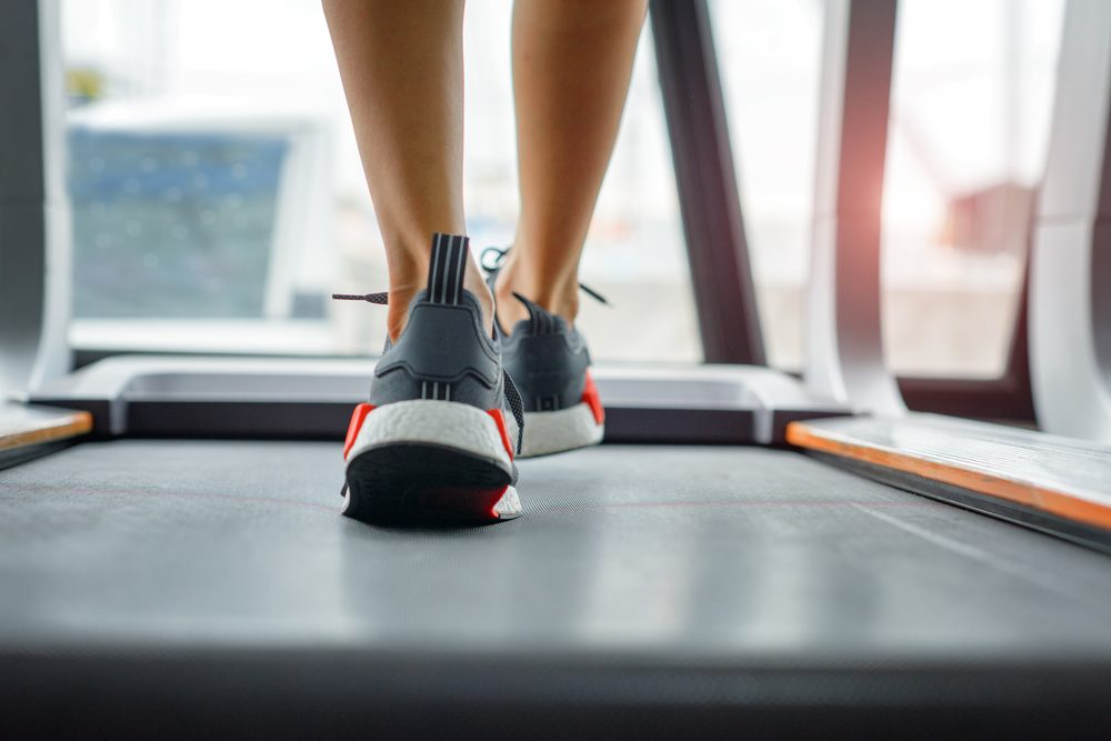 weight of toe of woman press down on the belt of treadmill while jogging in gymnasium