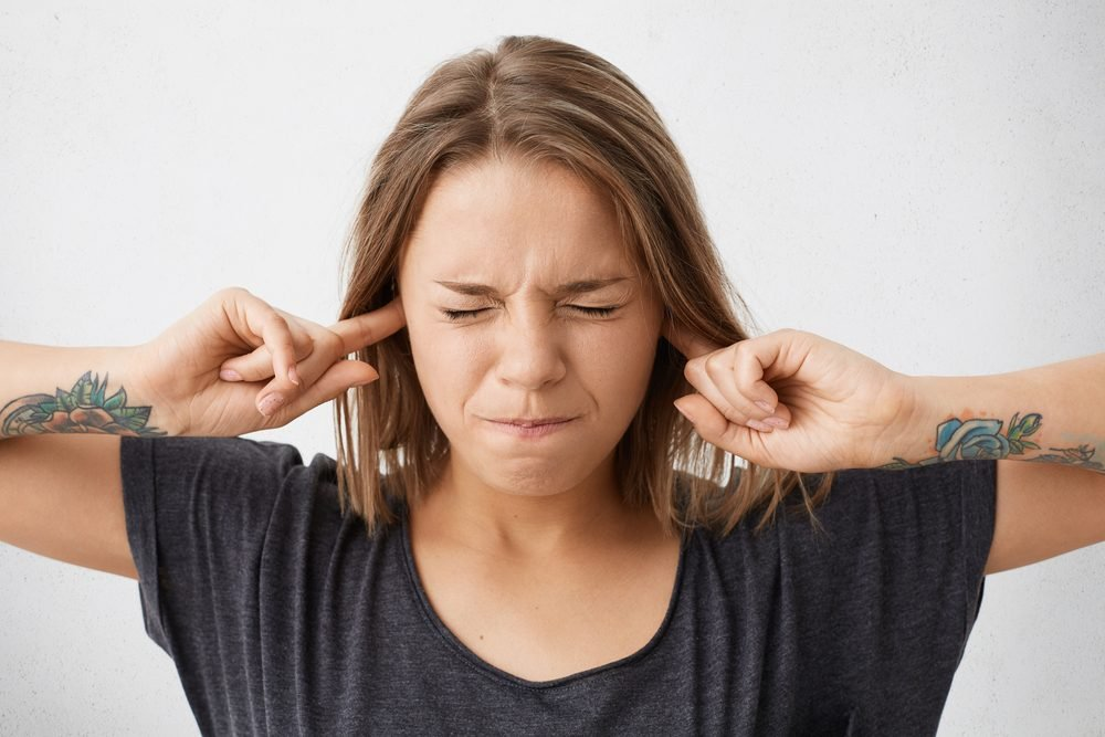 Close up portrait of angry stressed out young woman plugging ears with fingers and closing eyes tight, irritated with loud annoying noise, having headache or migraine. Negative human emotions