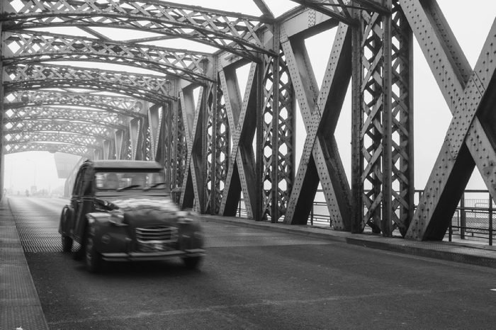 Old blue vintage car driving on the asphalt road of the city bridge on a foggy day in Dieppe, France. Old bridge tunnel metal structure. Urban scene, city life, transport and traffic concept. Toned