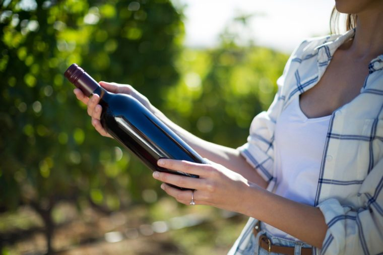 Mid section woman holding wine bottle at vineyard during sunny day