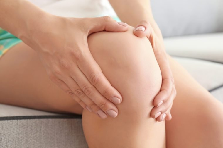 Young woman suffering from pain in leg at home, closeup