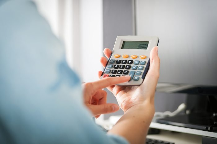 Woman at home office using calculator and computer, calculating budget
