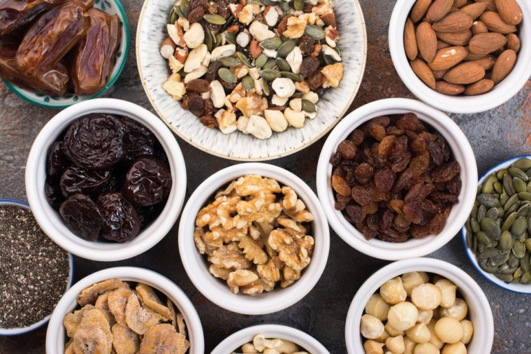 Top view of grain free paleo granola and ingredients , different nuts and raisins, dates, seed on the grey stone background, top view