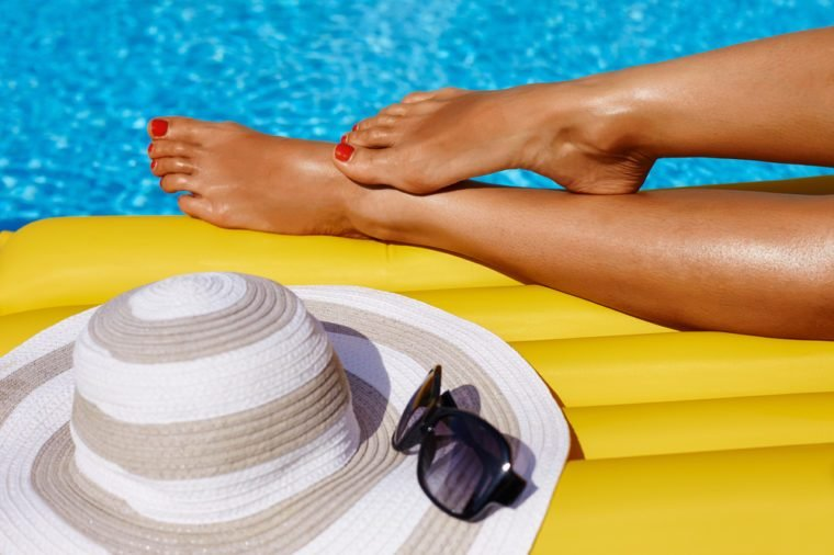 Portrait of beautiful tanned woman relaxing in bikini in swimming pool. Legs close up. Gel polish red pedicure. Hot summer day and bright sunny light.