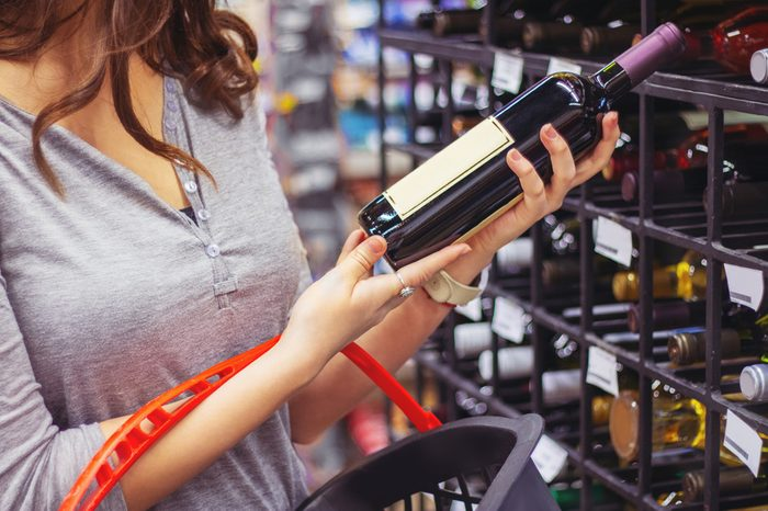 Woman buying and holding bottle of wine