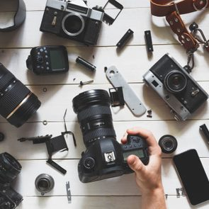 Man hand Holds Digital Camera On Table Next To Lenses And Accessories On White Wooden Background. Top View