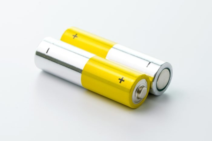 Two yellow AA size batteries isolated on white backgraound