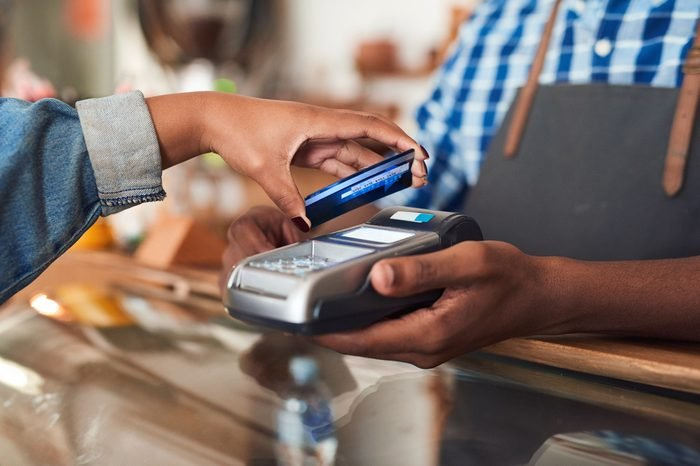 Closeup of a customer using her credit card and nfs technology to pay a barista for her purchase at a cafe