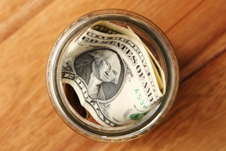 A savings jar filled with american dollars on a wooden table top.