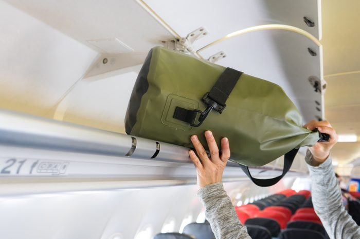 Passenger woman putting luggage into overhead locker on airplane (Selective focus)