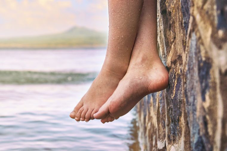 Young girl's wet bare feet dangling from the stone jetty