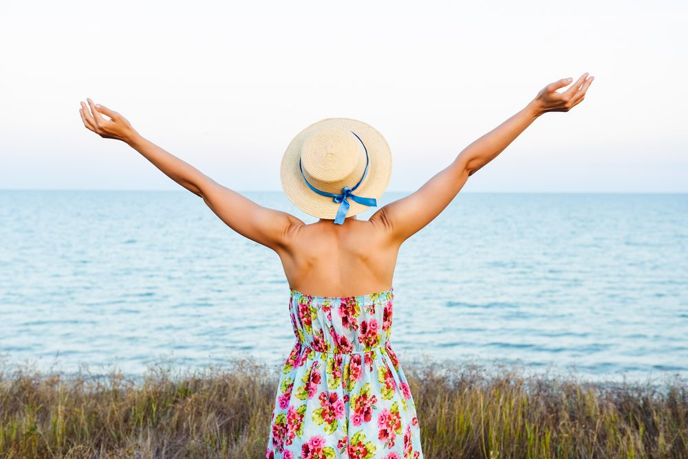 Young woman arms raised up to sky, celebrating freedom. Positive emotions feeling life perception success, peace of mind concept. Free Happy girl in summer meadow enjoying sea skyline. Text space.