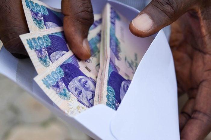Five hundred naira notes in envelope in Dark skin fingers