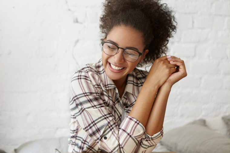 Positive human facial expressions and emotions. Indoor shot of cute charming Afro-American girl wearing stylish plaid shirt and eyeglasses, closing eyes in pleasure and excitement, smiling cheerfully