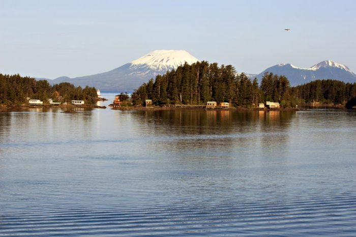 A landscape photo with water in the foreground showing sunrise on Mount Edgcome, Sitka, Alaska