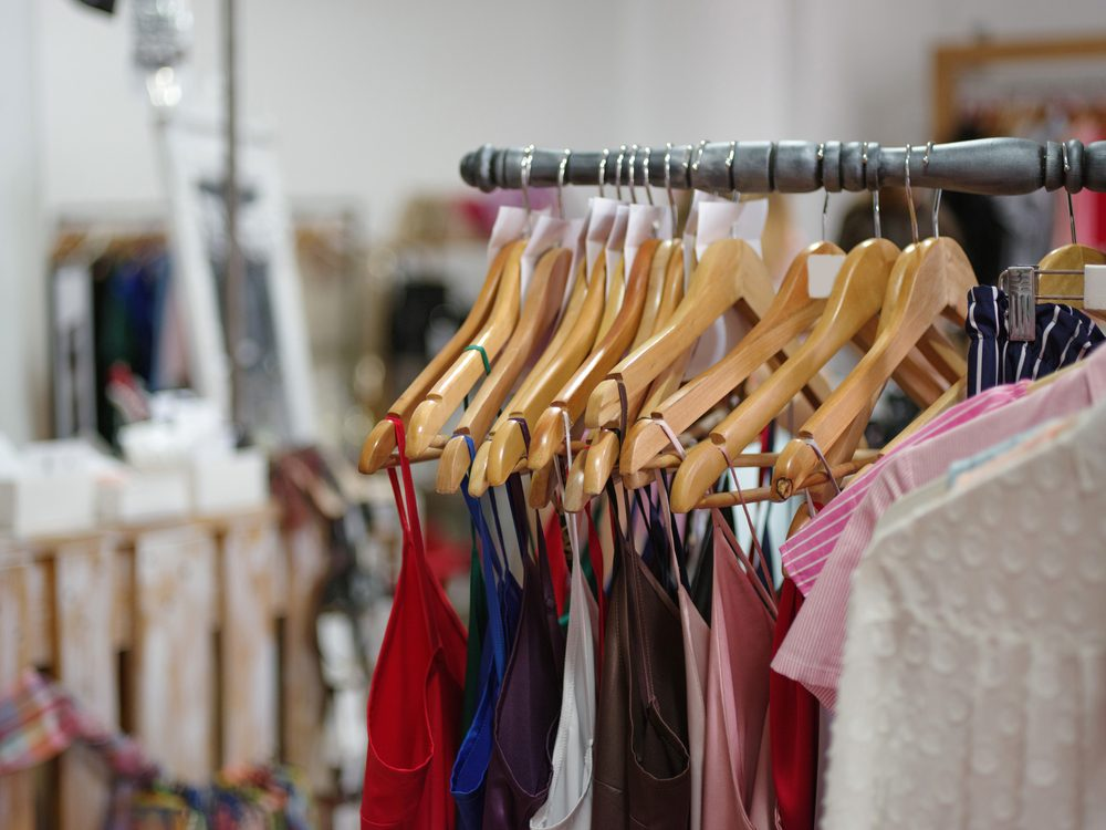 A big assortment colorful clothes for women on a shop background. Various fashionable color shirts and dresses in a expensive boutique. Luxury and stylish garment on hangers. Fashion concept.