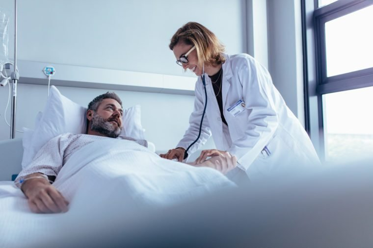 Hospitalized man lying in bed while doctor checking his pulse. Female physician examining male patient in hospital room.