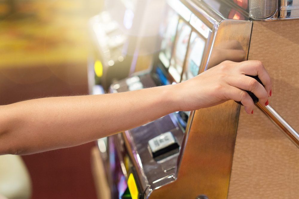 Woman pulling the handle on a slot machine in a casino. Gambling, luck, taking risk and winning jackpot concept. Gambler playing in Las Vegas or Atlantic City.