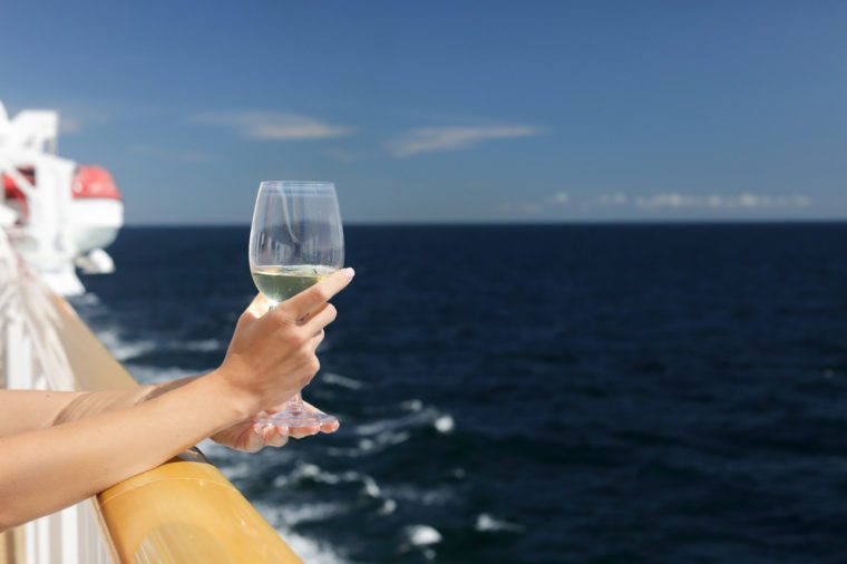 Female hand holds a glass of white wine on a cruise liner