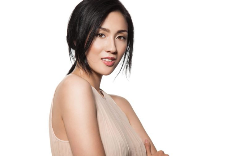 Young stylish asian woman in beige dress with clean skin and natural make-up looks into the camera isolated on white background