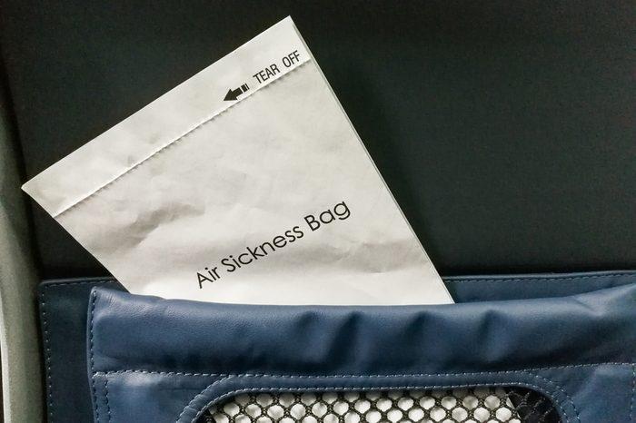 Air sickness bag tucked behind airplane seat pocket for nauseous passenger