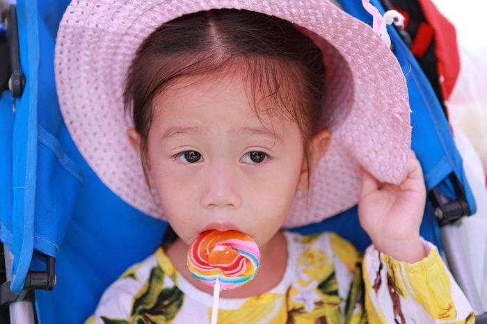 Close-up Beautiful cute little girl wear straw hat eating lollipop