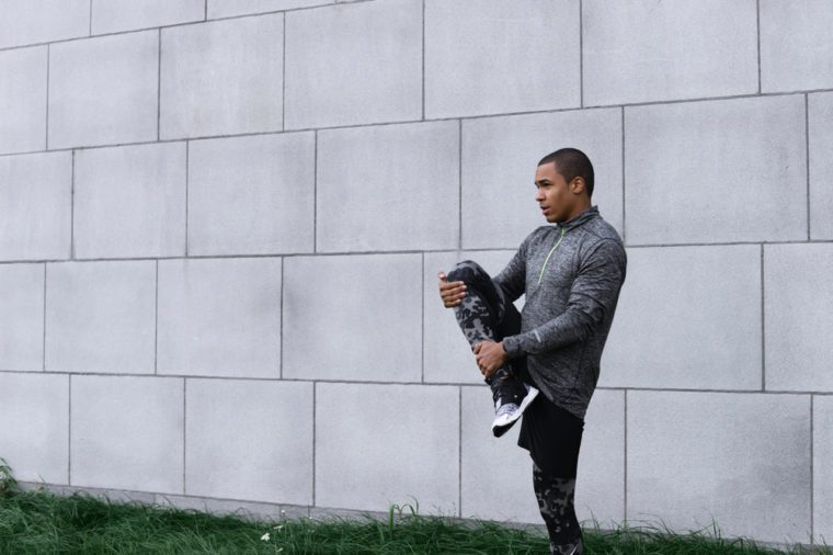 Picture of stylish slim young dark-skinned male jogger or runner wearing leggings, running shoes and fleece jacket warming up legs outdoors before morning cardio workout routine. Sports and fitness